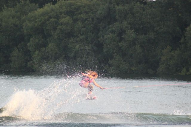 Women wakeboards across the lake, ready for a jump