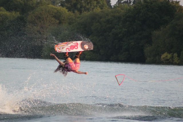 Women performs a wakeboarding move in the air