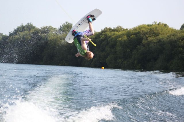 Man performing a wakeboard move in the air upside down